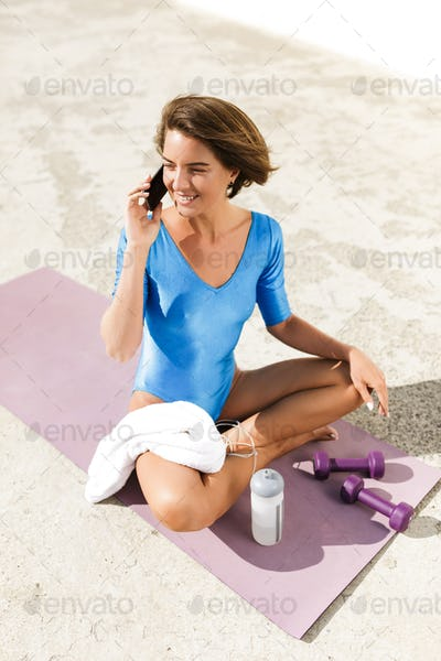 Smiling woman in blue swimsuit sitting on yoga mat and talking on cellphone happily looking aside
