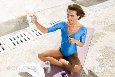 Nice woman in blue swimsuit sitting on yoga mat amazedly looking in cellphone while taking selfie