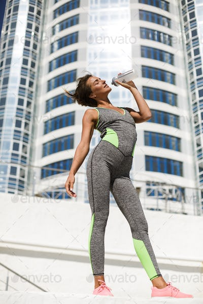 Smiling woman in modern gray sport suit drinking water with high building on background