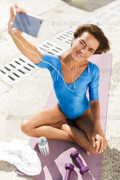 Smiling woman in swimsuit on yoga mat dreamily looking in her cellphone while taking selfie