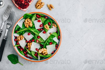 Spinach salad bowl with pomegranate seeds, walnuts and cheese slices.
