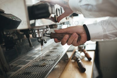 Man hands working with coffee machine at cafe