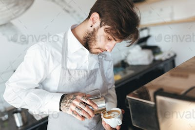 Barista in apron and white shirt making coffee at his workplace in coffee shop
