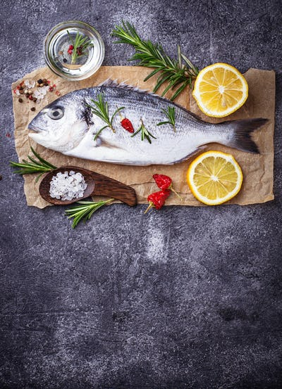 Uncooked dorado fish with rosemary and vegetables