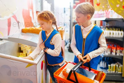Boy and girl in uniform playing sellers, playroom