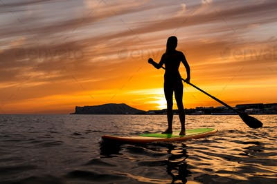 Stand up paddle boarding on a quiet sea with warm summer sunset colors