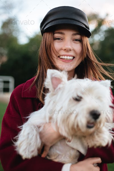 Joyful beautiful lady in black cap and coat happily looking in camera holding in hands her cute dog