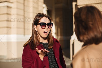 Young lady in sunglasses standing and amazedly looking at her friend on street