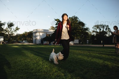 Young beautiful lady in black cap and coat joyfully walking in park with her small cute dog