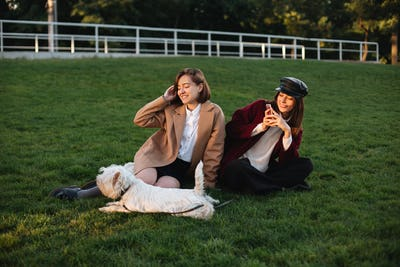 Pretty smiling girls sitting on grass and taking photos while spending time with cute dog in park