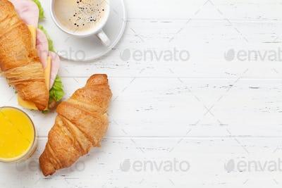 Coffee, orange juice and croissant sandwich