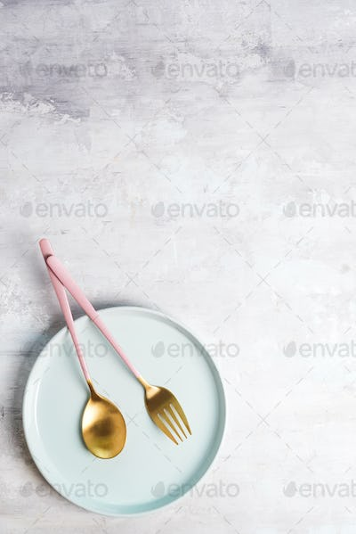New luxury Golden cutlery with blue plate on stone background. Top view. Pink knife and fork for a