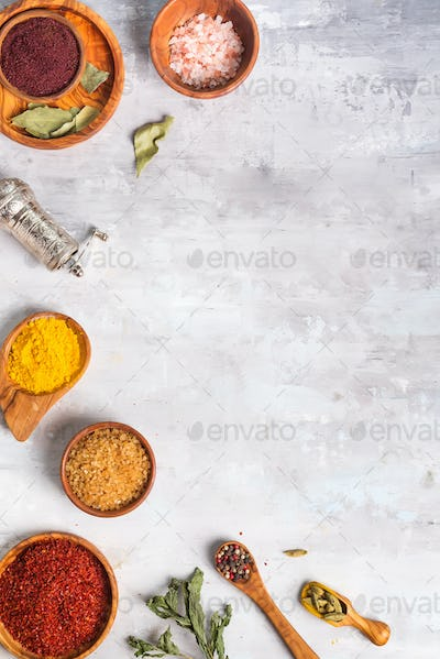 Dried herb and spice food in spoons and bowls on stone as frame, flat lay