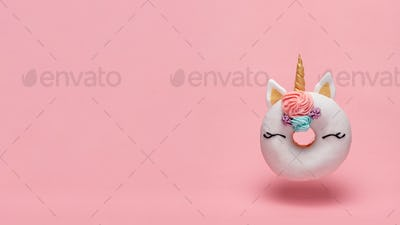 Unicorn donut flying, pink background, copy space