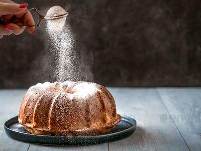 Female hand sprinkling icing sugar on muffin cake