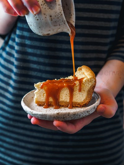 Cheesecake pouring caramel in female hands