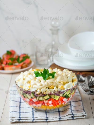 Layered crab salad with corn, cucumber, rice