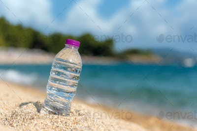 Bottle of fresh cold water on beach sand