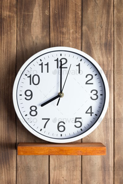 wall clock at shelf on wooden background
