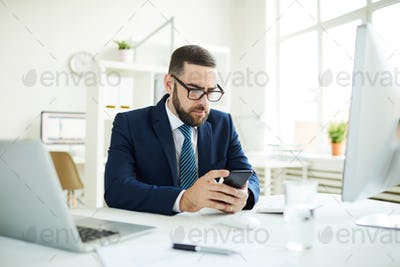 Businessman reading sms in office
