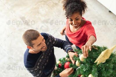 Young couple decorating xmas tree