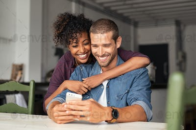 Happy couple looking at phone together