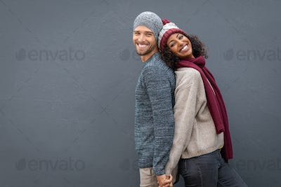 Happy couple in winter clothes leaning against back