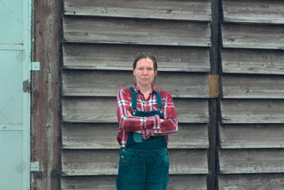 Portrait of female farmer in front of the farmhouse shed