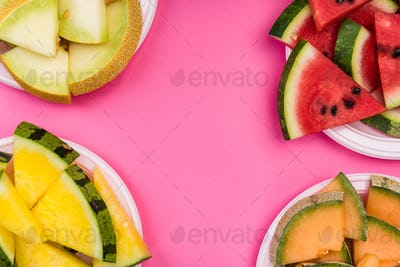 Watermelon and Melon Slices on Plate, Top View on Pink Pastel Ba