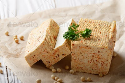 Soy Bean curd tofu on parchment paper with greens Non-dairy alte