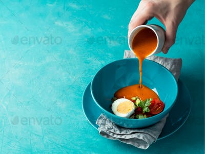 Hand pouring of Gaspacho soup in bowl