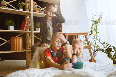 Little boys using different gadgets at home