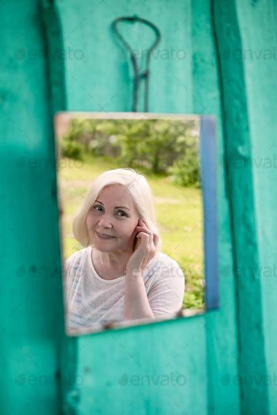 Attractive senior blonde woman looking at herself in mirror sitting outdoor at summer garden