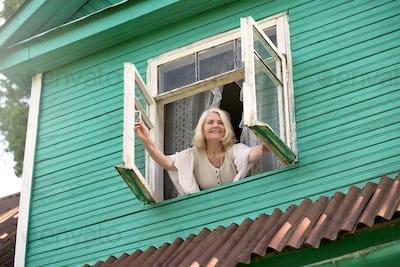 Senior blonde woman opening window inthe morning morning waking up.