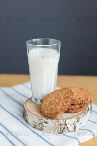 round brown wholegrain flour cookies and milk glass on striped white napkin on wooden table