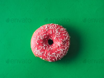 Top view of pink glazed donut on green background