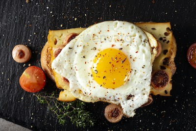 Open sandwich made with egg, cheese and sausages