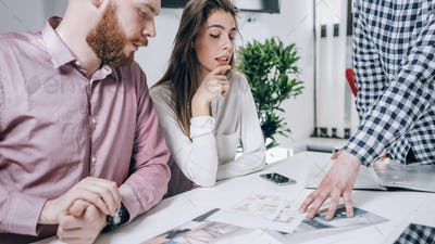 Couple in Real-Estate Agency Talking to Real Estate Agent