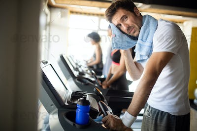 Athletic young man having rest after running training, drinking water at gym, standing at treadmill