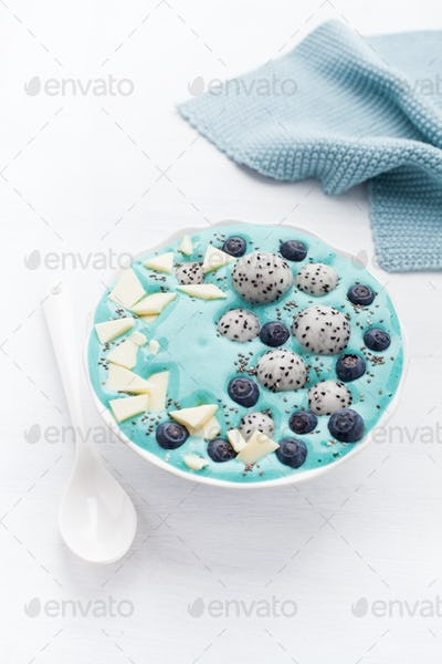 healthy blue spirulina smoothie bowl with blueberry, white choco