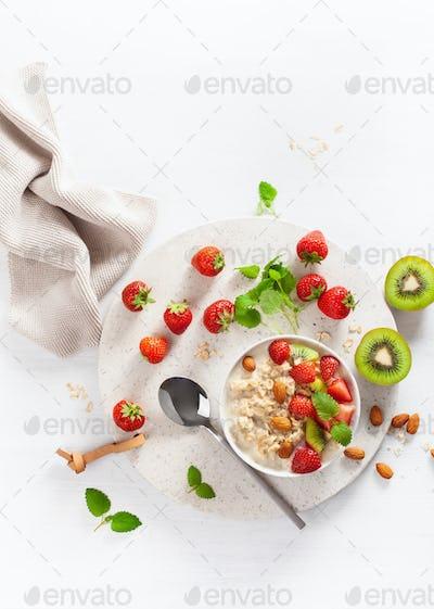 healthy breakfast oatmeal porridge, strawberry, nuts. Top view