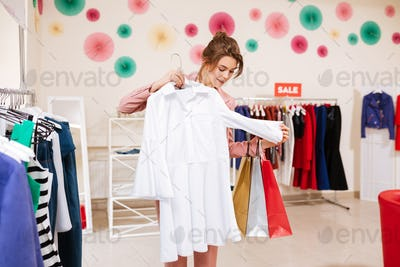 Beautiful smiling girl go shopping and choose white dress in clothes store
