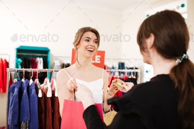 Pretty girl in white top making a purchases in clothes store with sale clothes rack on background