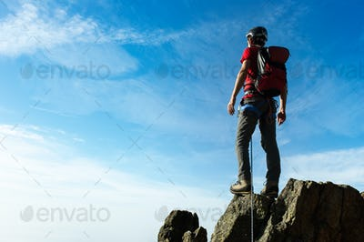 Climber arrive on the summit of a mountain peak. Concepts: victo