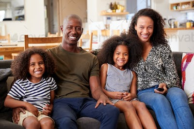 Portrait Of Smiling Family Sitting On Sofa At Home Relaxing Together
