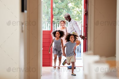 Grandparents With Grandchildren Returning Home From Shopping Trip Carrying Grocery Bags