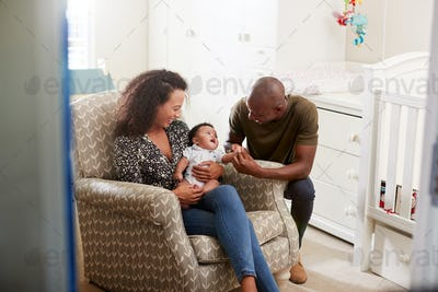 Loving Parents Sitting In Chair Cuddling Baby Son In Nursery At Home