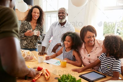 Grandparents Sitting At Table With Grandchildren Playing Games As Family Prepares Meal