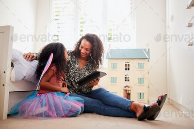 Mother With Daughter Sitting On Bed In Childs Bedroom Using Digital Tablet Together