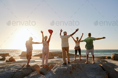 Rear View Of Senior Friends Standing On Rocks On Vacation With Arms Outstretched
